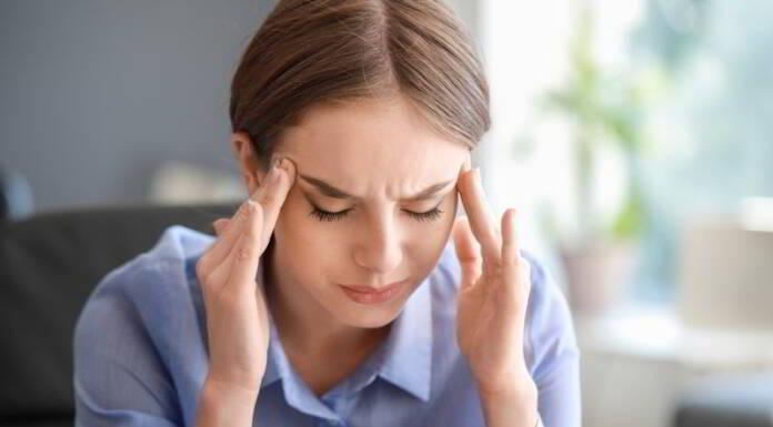 Młoda kobieta z migreną oczną trzymająca się za skronie